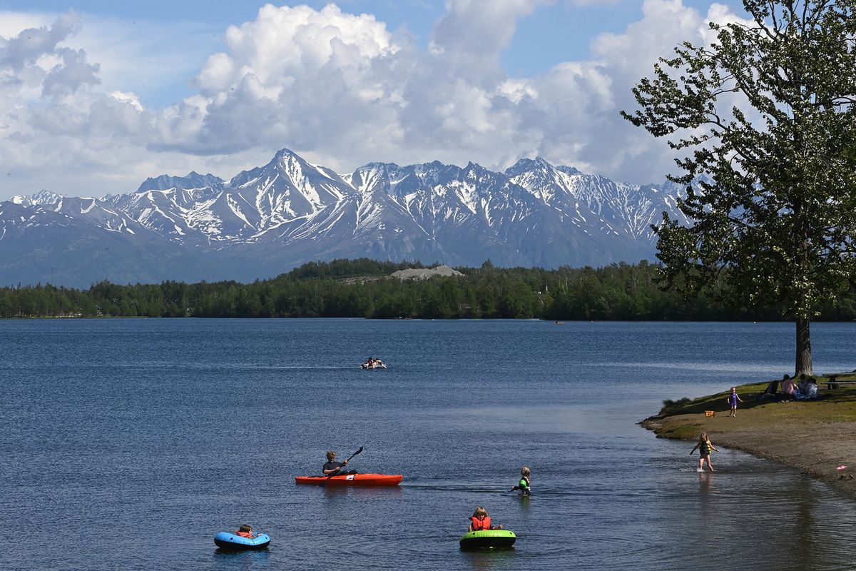Clouds build over the Chugach Mountains on Sunday, June 6, 2021, as people take to the water at Newcomb Park on the shore of Wasilla Lake. (Bill Roth / ADN)