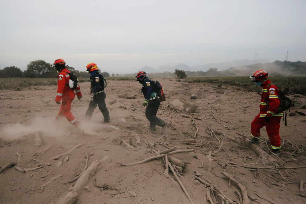 Rescue workers walk through an area affected by eruption from Fuego volcano in the community of San Miguel Los Lotes in Escuintla, Guatemala June 4, 2018. REUTERS/Luis Echeverria