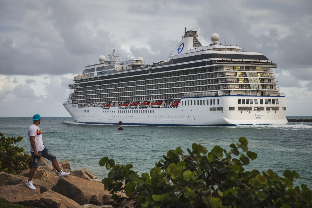 People watch as a cruise ship departs to the Atlantic Ocean from South Pointe Park in Miami Beach on Wednesday. (Photo for The Washington Post by Scott McIntyre)