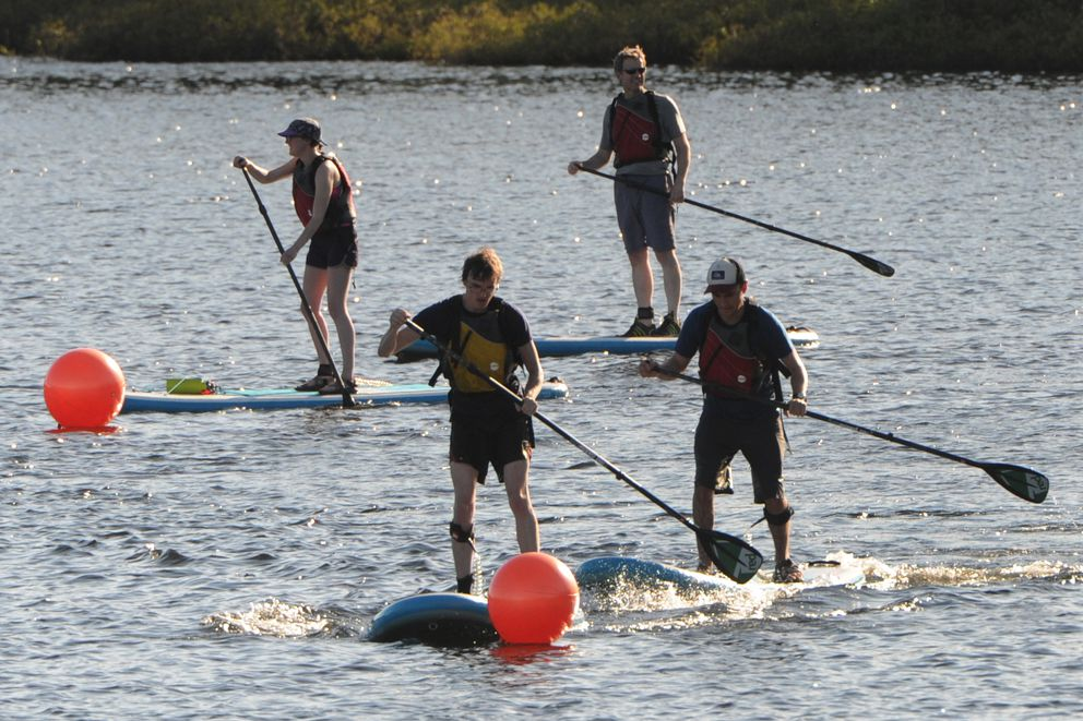 Ty Morrison and Travis Smith race each other while taking a stand-up paddleboard lesson at DeLong Lake. (Bill Roth / Alaska Dispatch News)​