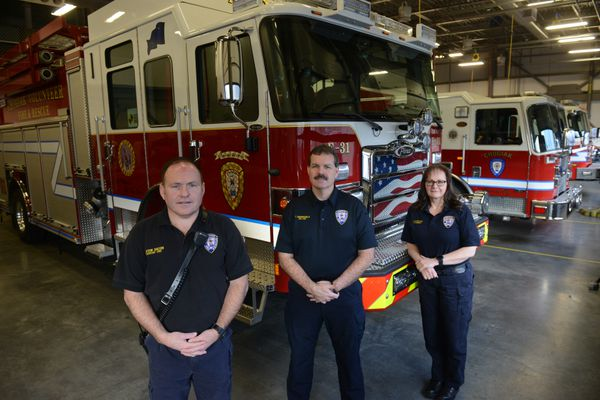 Members of the Chugiak Volunteer Fire and Rescue Company, Clifton Dalton, assistant chief, Tim Benningfield, fire chief, and Virginia McMichael, administrative officer, pose in front of one of the fire trucks at Station 35 in Chugiak, Alaska on Wednesday, Nov. 1, 2017. (Bob Hallinen / Alaska Dispatch News)