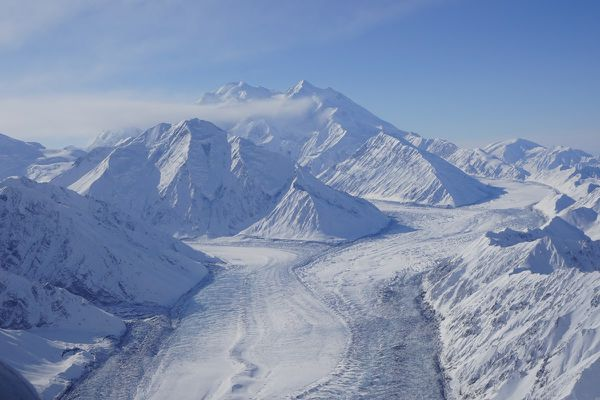 Photograph of the upper part of the Muldrow Glacier, with Denali in the background, in March 2021. Tributaries of the Muldrow Glacier, the Traleika and Brooks glaciers, are seen feeding into the main trunk in the center of the photograph. The edges of the glacier in the foreground display particularly heavy crevassing. (National Park Service photo)