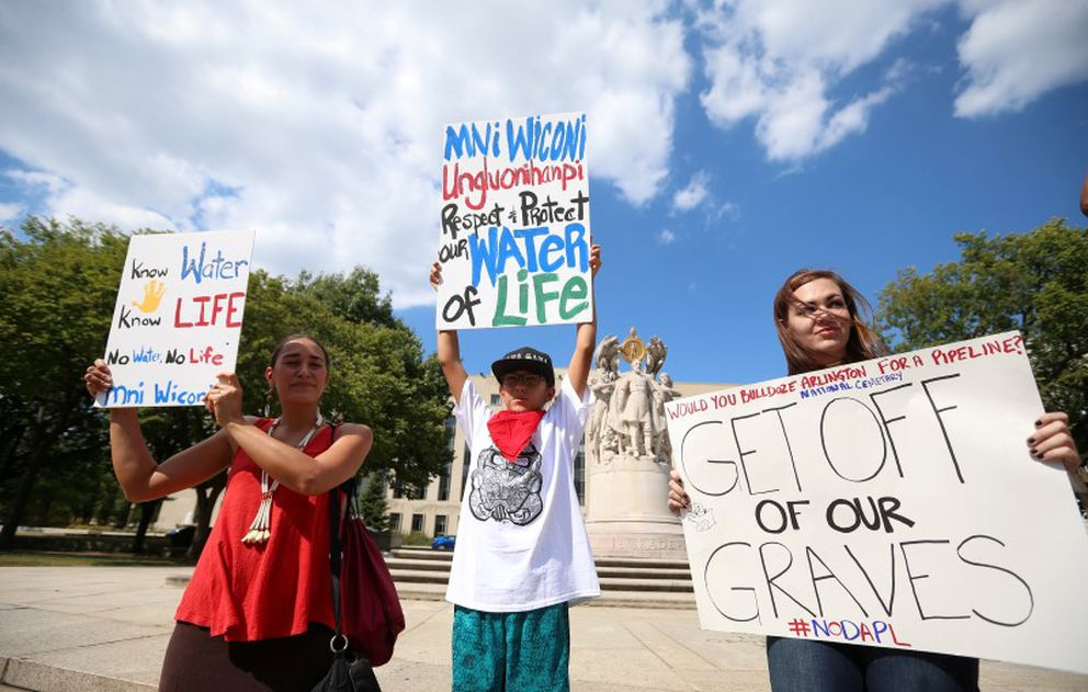 Protesters hold signs outside the U.S. District Court in Washington, where a hearing was being held to decide whether to halt construction of an oil pipeline in parts of North Dakota where a Native American tribe says it has ancient burial and prayer sites, on Sept. 6, 2016. (Kevin Lamarque / Reuters)