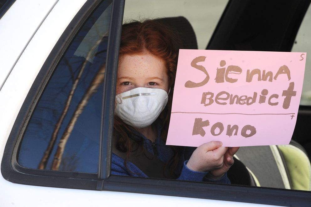 Second grade student Sienna Benedict, 7, holds up a sign that teachers used to retrieve her personal belongings at Sand Lake Elementary on Tuesday, May 5, 2020, during the COVID-19 pandemic. (Bill Roth / ADN)