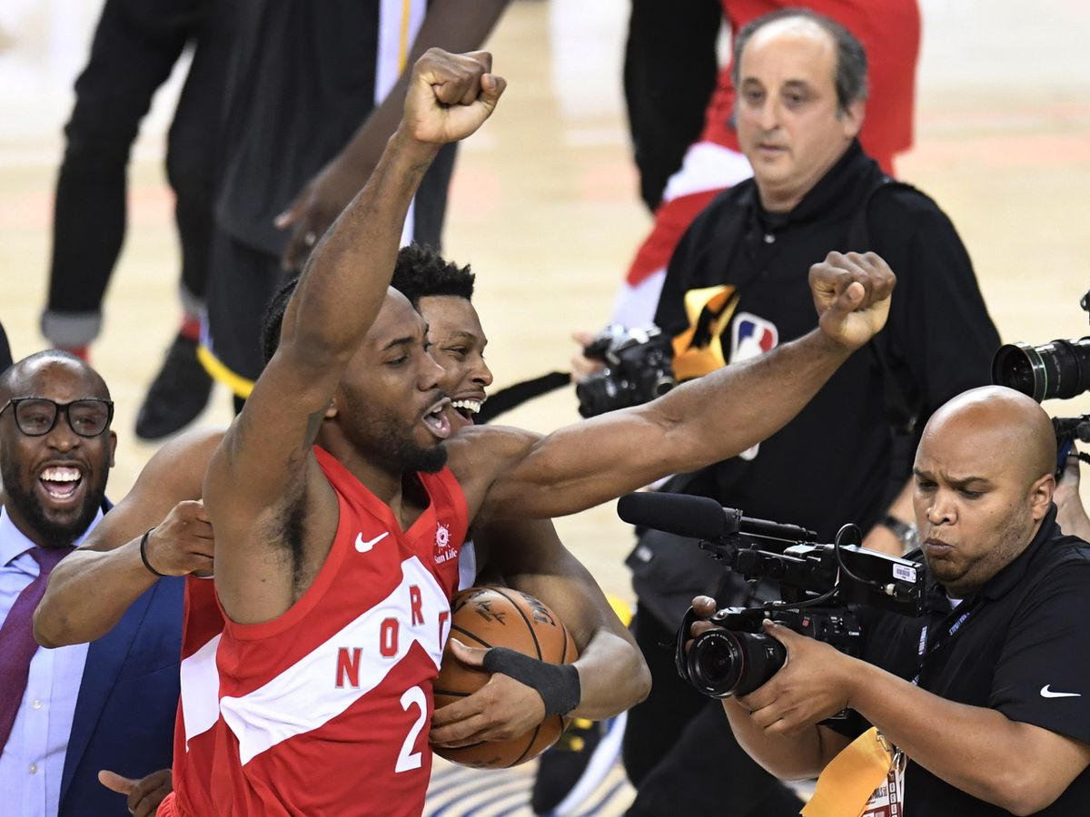 Toronto Raptors forward Kawhi Leonard (2) and guard Kyle Lowry, back, celebrate after the Raptors defeated the Golden State Warriors 114-110 in Game 6 of basketball's NBA Finals, Thursday, June 13, 2019, in Oakland, Calif. (Frank Gunn/The Canadian Press via AP)
