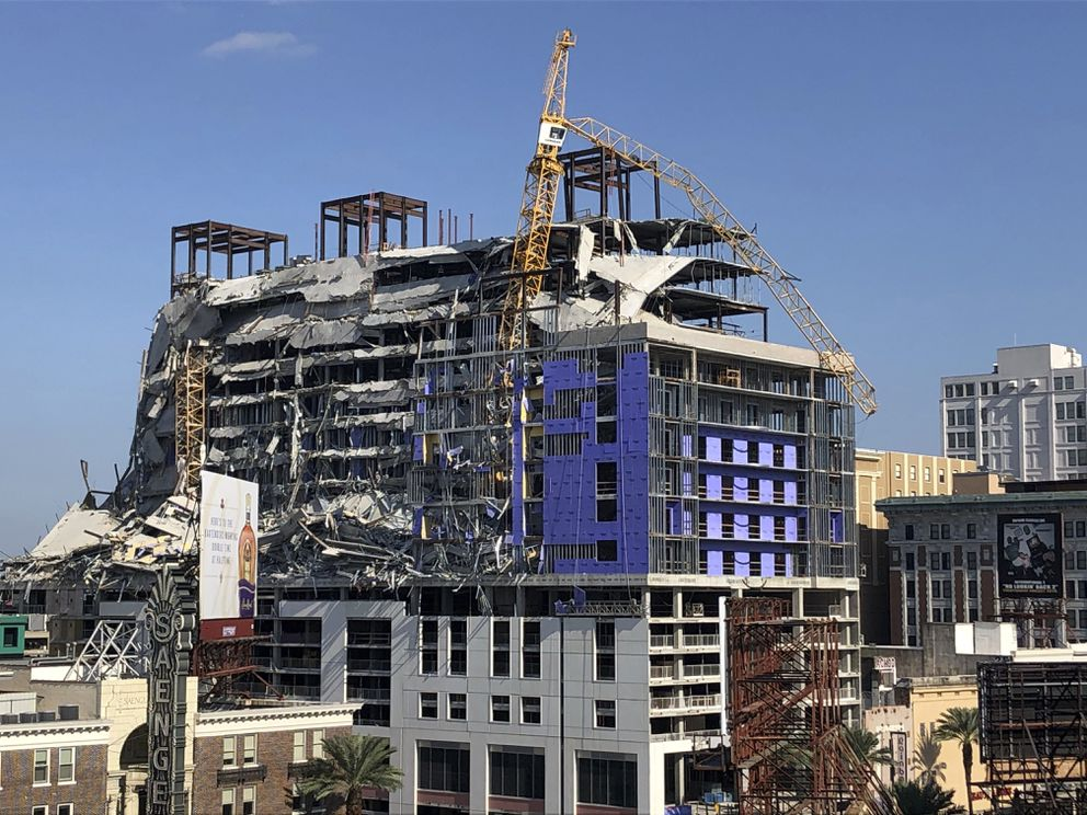 A large crane appears to dangle atop the partially collapsed Hard Rock Hotel after officials set off explosions to topple two cranes on Sunday, Oct. 20, 2019, in New Orleans. (AP Photo/Rebecca Santana)