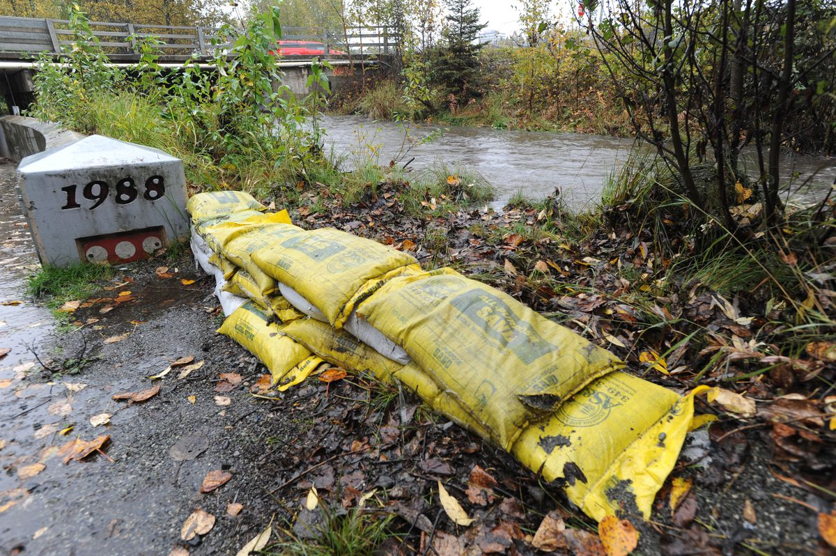 Sand bags are placed to hold back high water from Chester Creek so it doesn't spill onto the Chester Creek trail, Sept. 20, 2019. (Anne Raup / ADN)
