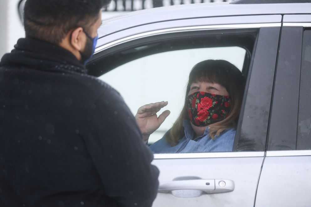 Barb Dexter talks with her student Keoni Sanele at his home after delivering gift cards to him through the window of her car in Anchorage on Tuesday, Dec. 15, 2020. Dexter is a secondary teacher specialist with the Child in Transition program. She also helps coordinate The Back on Track program which is a credit recovery program for students who are at high risk of not graduating. (Emily Mesner / ADN)