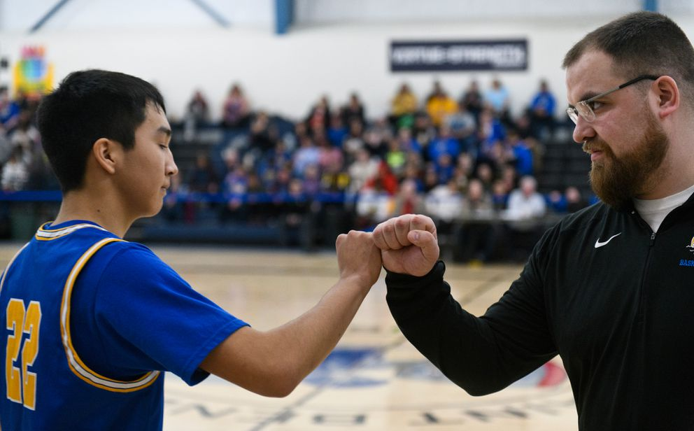 Kotzebue player Devin Sheldon bumps fists with Barrow coach Daniel Thomas during player introductions at Lumen Christi High School in Anchorage during the the Class 3A Western Conference tournament. (Marc Lester / ADN)