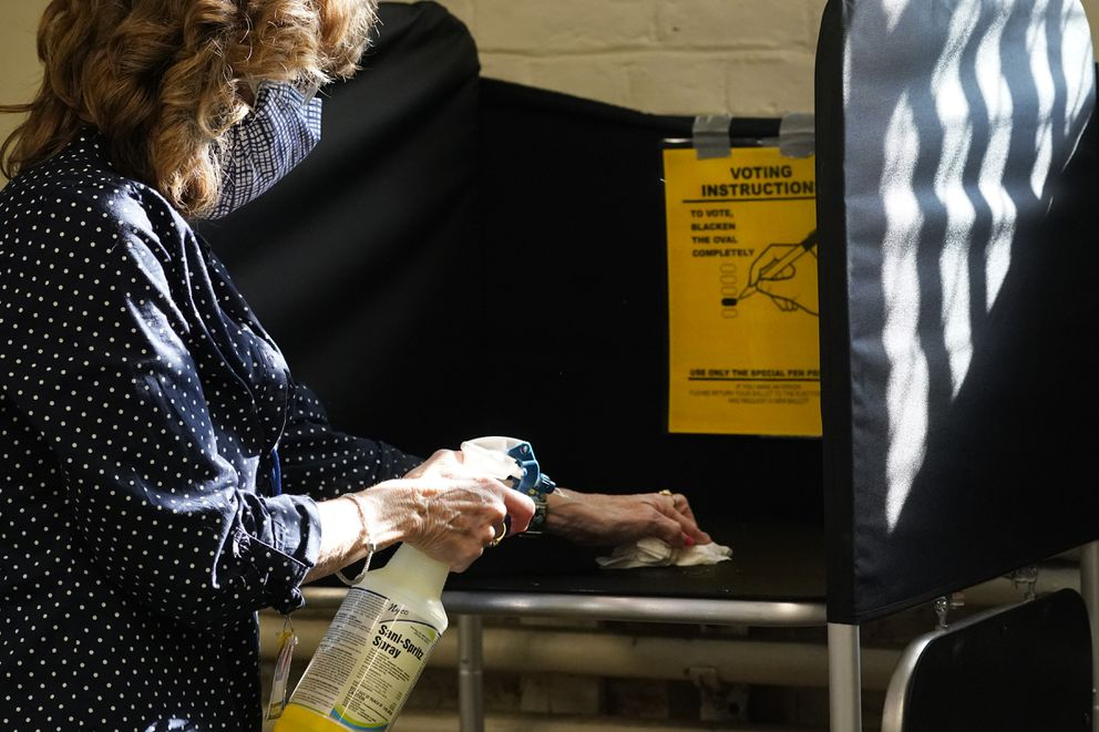 FILE - In this Oct. 22, 2020, file photo, election clerk Cheryl Lupi sanitizes a voting booth inside Haverhill City Hall during early in-person voting in Haverhill, Mass. The United States is approaching a record for the number of new daily coronavirus cases in the latest ominous sign about the disease's grip on the nation. (AP Photo/Elise Amendola, File)