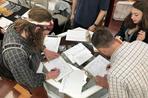 Juneau residents sign a petition seeking to recall Gov. Mike Dunleavy from office on Thursday, Aug. 1, 2019, at the Planet Alaska art gallery in Juneau. (James Brooks / ADN)