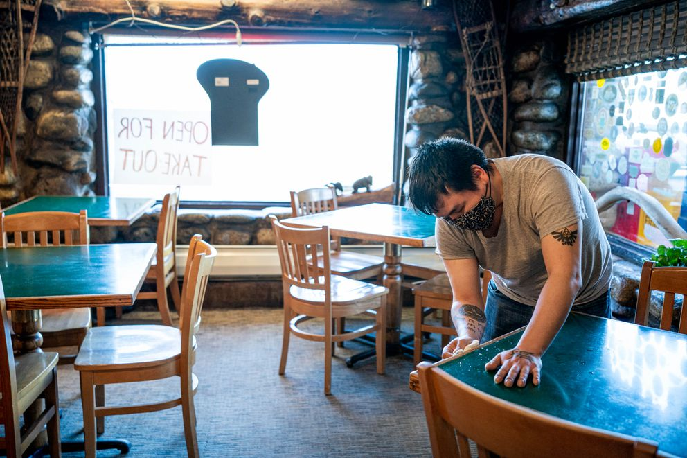 Paul Hobson sanitizes tables at Gwennie's Old Alaska Restaurant on Saturday, April 25, 2020. The restaurant plans to open for dine-in service on Monday. (Loren Holmes / ADN)