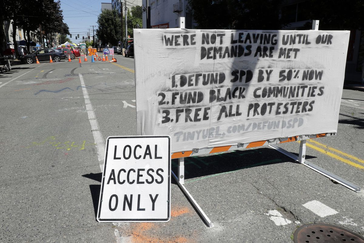A sign on a street barricade lists some of the demands of protesters in what has been named the Capitol Hill Occupied Protest zone in Seattle, Monday, June 22, 2020. (AP Photo/Ted S. Warren)
