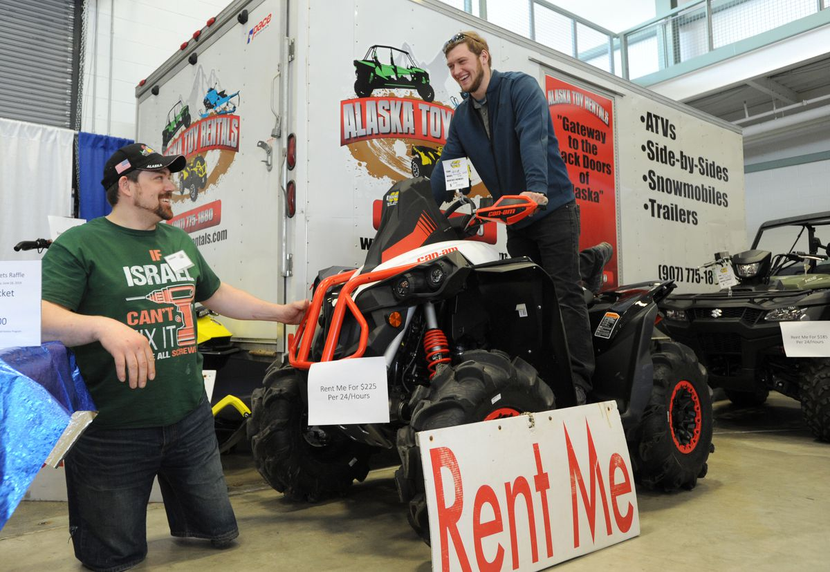 Israel Hale talks with Dallas Byler about a 4-wheeler Hale has for rent. Hale, owner of Alaska Toy Rentals in Palmer, had a booth at the Mat-Su Outdoorsman Show on March 22, 2019. (Anne Raup / ADN)
