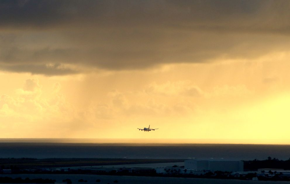 FILE - In this April 6, 2020 file photo, a plane lands as the sun sets over the Pacific Ocean in Honolulu. (AP Photo/Caleb Jones, File)