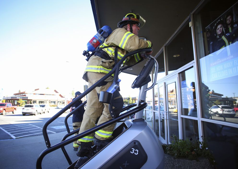 AFD's Blayde Briske holds on to the stepmill's handle bars as he nears the 11-minute mark during the Annual Firefighter Step Mill Challenge outside The Alaska Club for Women on Sept. 11, 2020. Firefighters and first responders took turns climbing as many flights of stairs as possible in 11 minutes in honor of the anniversary of the 9/11 terrorist attacks. (Emily Mesner / ADN)