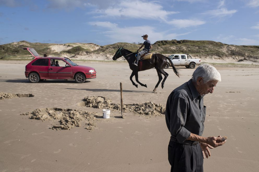 Jose Rocha gathers yellow clams in Barra del Chuy, Uruguay. (Washington Post photo by Carolyn Van Houten)