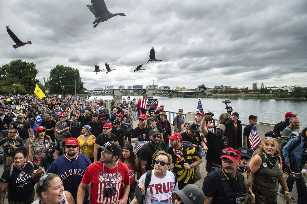 Members of the Proud Boys and other right-wing demonstrators march along the Willamette River during an 'End Domestic Terrorism ' rally in Portland, Ore., on Saturday, Aug. 17, 2019. Police have mobilized to prevent clashes between conservative groups and counter-protesters who converged on the city. (AP Photo/Noah Berger)