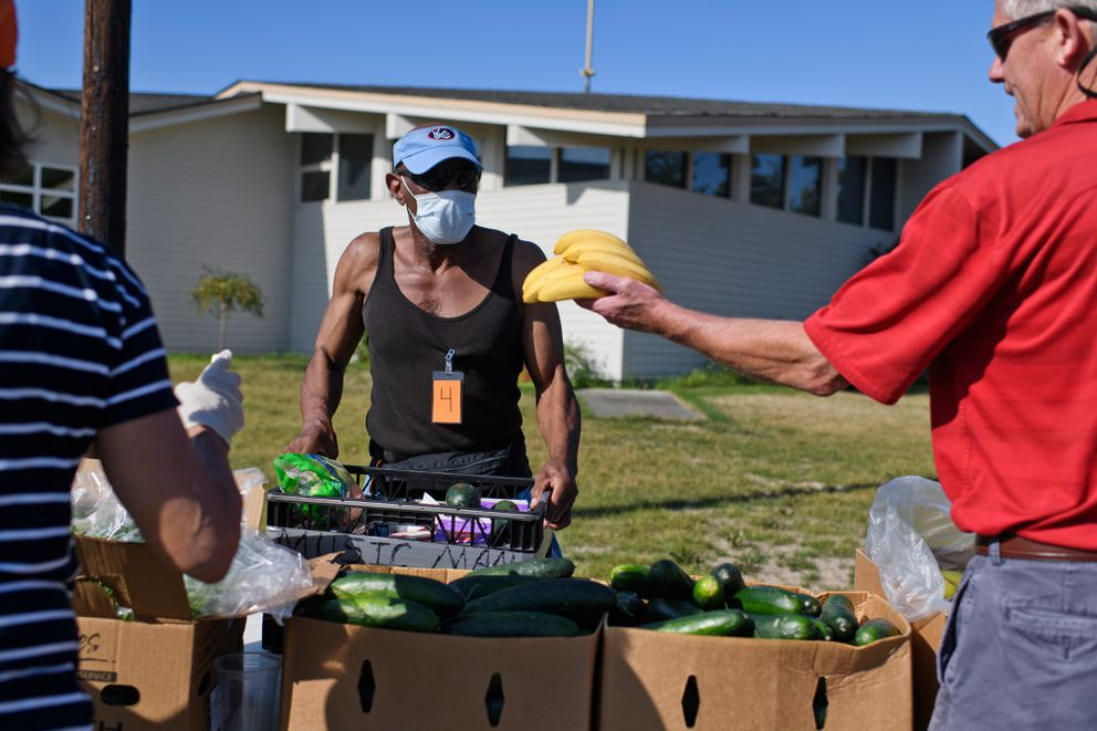 """Alonzo Hill, 65, picks up food from the Lutheran Social Services mobile food pantry on August 6, 2019. Hill, who said he's disabled, no longer receives the Alaska Senior Benefits Payment Program assistance. """"That $75 a month, I was using that for the food I need and stuff I need for around the house,"""" he said. (Marc Lester / ADN)"""