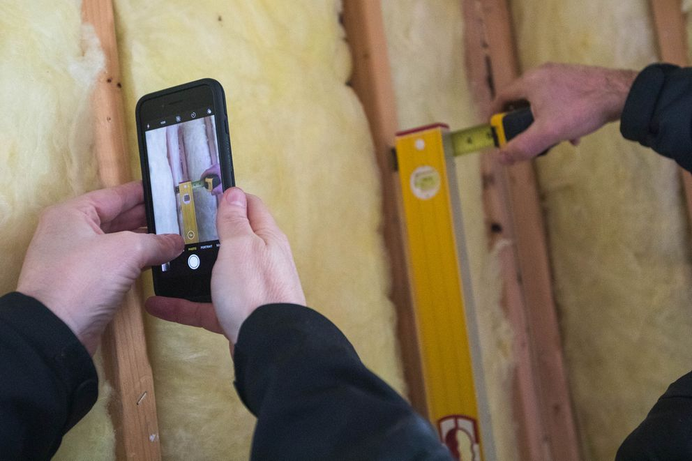 Eagle River homeowner Duncan Whitney takes a picture of a level, held by structural engineer Jake Horazdovsky, that shows an out-of-plumb wall in Whitney's home on Tuesday. (Loren Holmes / ADN)