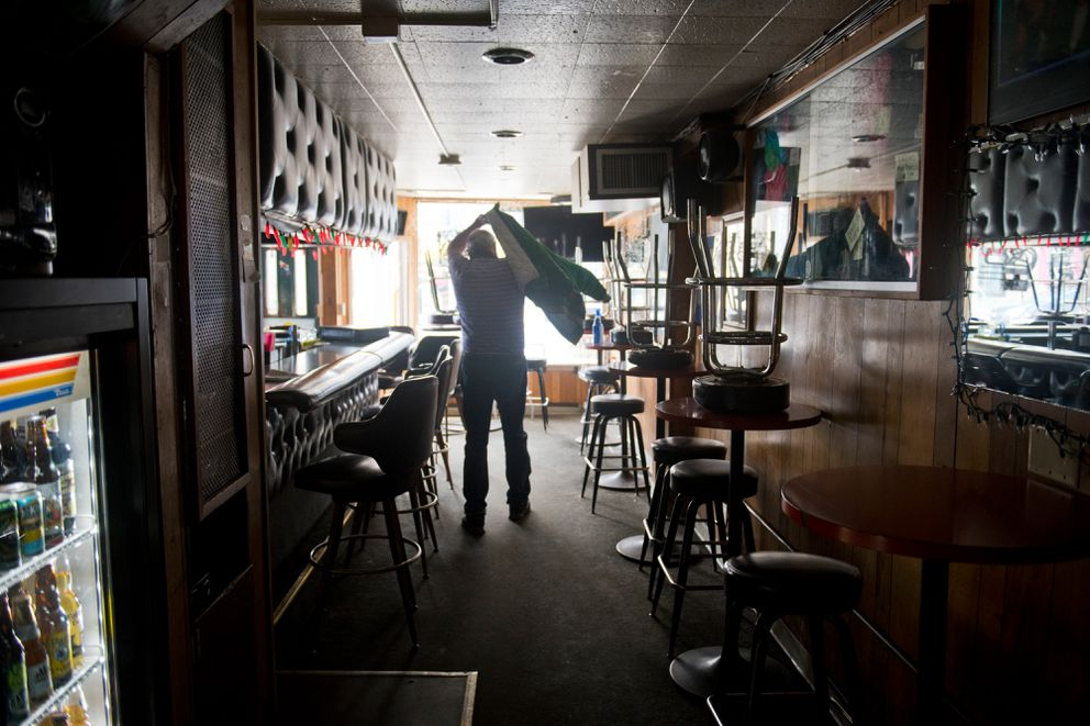 Darwin's Theory owner Darwin Biwer Jr. puts on his coat to leave the downtown bar that he's preparing to reopen. (Marc Lester / ADN)