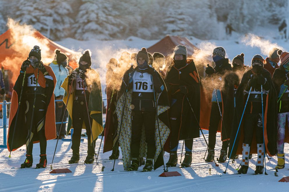Skiers try to stay warm before the start of the race. (Loren Holmes / ADN)