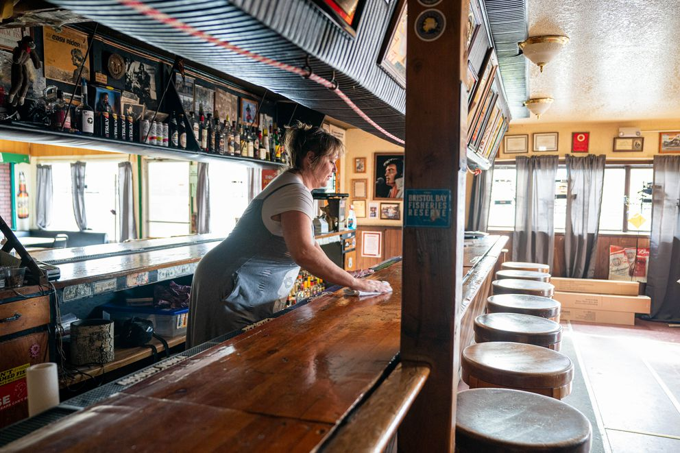 Lead bartender Jo Rainwater cleans the bar at Birchwood Saloon on Friday, April 30, 2021 in Chugiak. Since the Anchorage Assembly has lifted many COVID-19 restrictions, the bar plans on opening on Wednesday for Cinco de Mayo. (Loren Holmes / ADN)