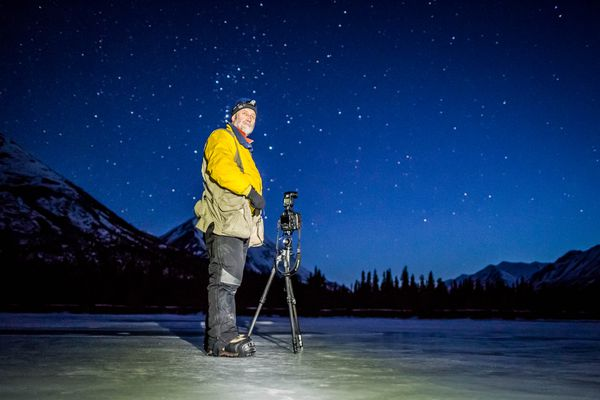 Official Iditarod photographer Jeff Schultz sets up a shot on the Tatina River between the Dalzell Gorge and Rohn on March 3, 2014.