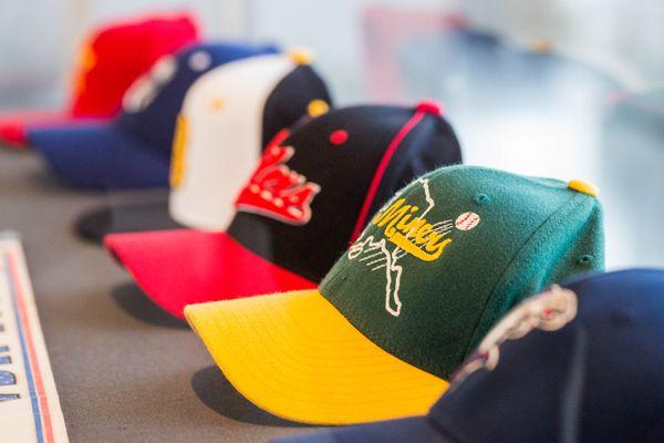 Baseball hats from teams in the Alaska Baseball League, part of the