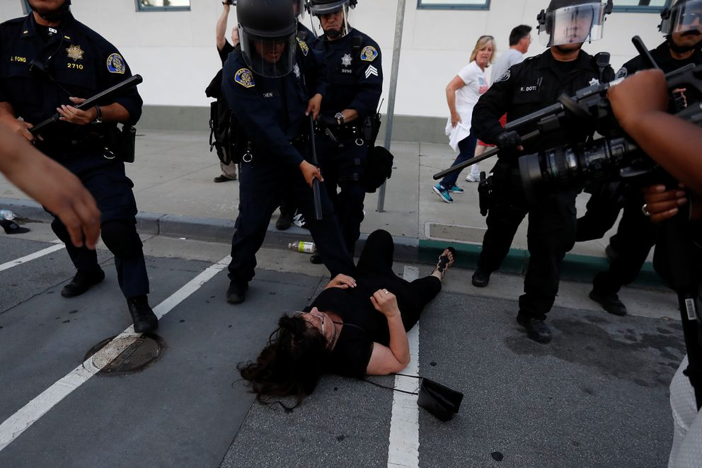 A woman falls as police officers move the line during a demonstration against Republican U.S. presidential candidate Donald Trump outside his campaign event in San Jose, California, U.S. June 2, 2016. REUTERS/Stephen Lam