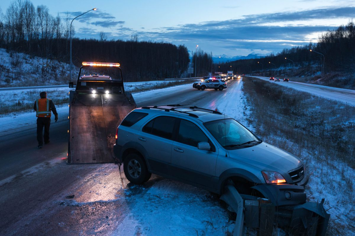 Aurora Towing operator Roderick Gawreluk pulls a car off the guardrail on the Glenn Highway near Mirror Lake early Wednesday morning. (Loren Holmes / Alaska Dispatch News)