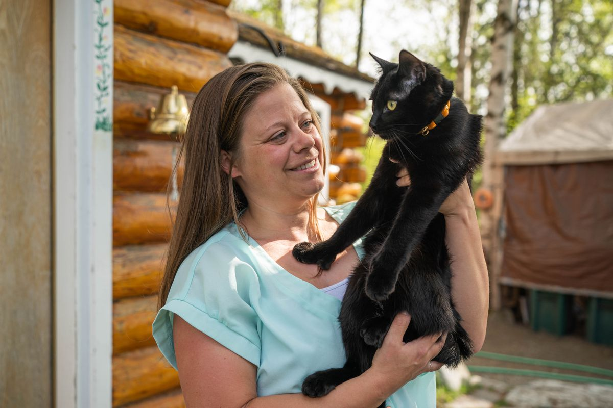 """Sarah Wilcox holds her cat Sirius outside her home Wednesday, May 20, 2020 in Spenard. Wilcox and her husband rescued the cat in late March after their other cat died. """"He is the best,"""" she said. """"He is my little buddy. I don't know if I would be OK without him."""" (Loren Holmes / ADN)"""