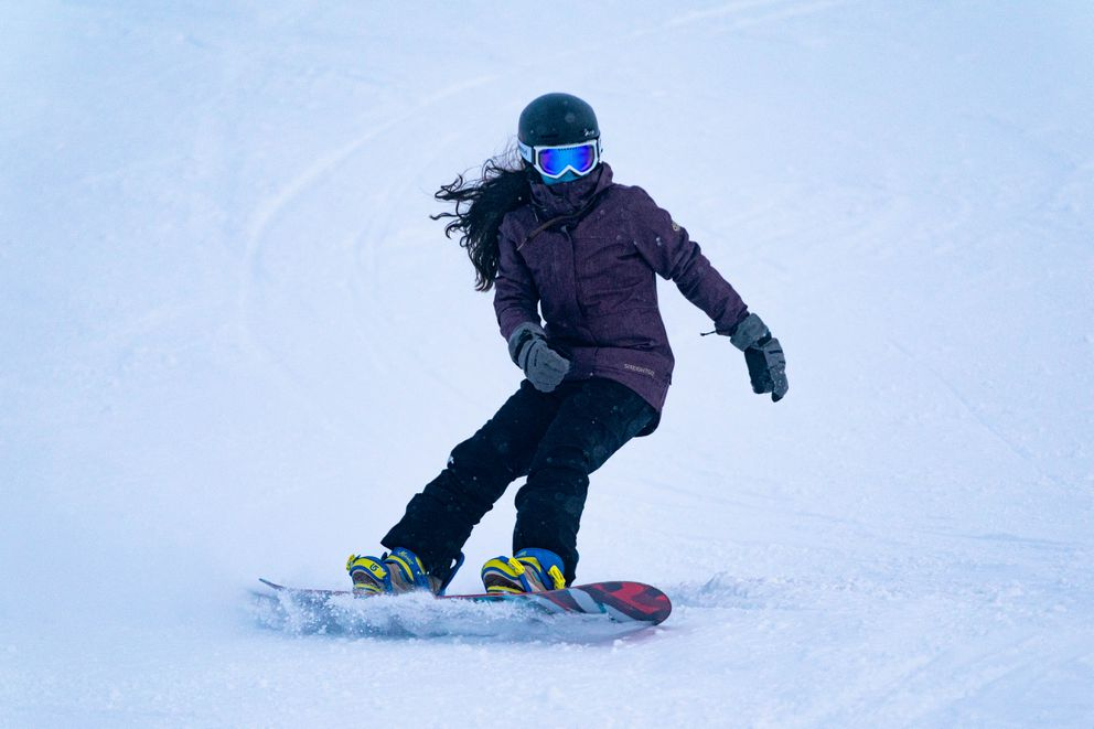 A snowboarder wears a mask while riding at Alyeska Resort on opening day. (Loren Holmes / ADN)