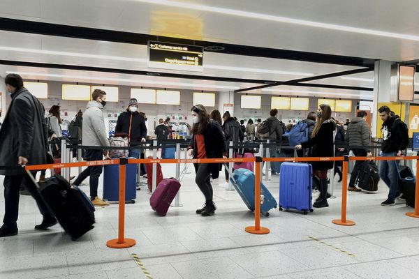 FILE - In this Dec. 20, 2020, file photo, passengers queue for check-in at Gatwick Airport in West Sussex, England, south of London. (Gareth Fuller/PA via AP)