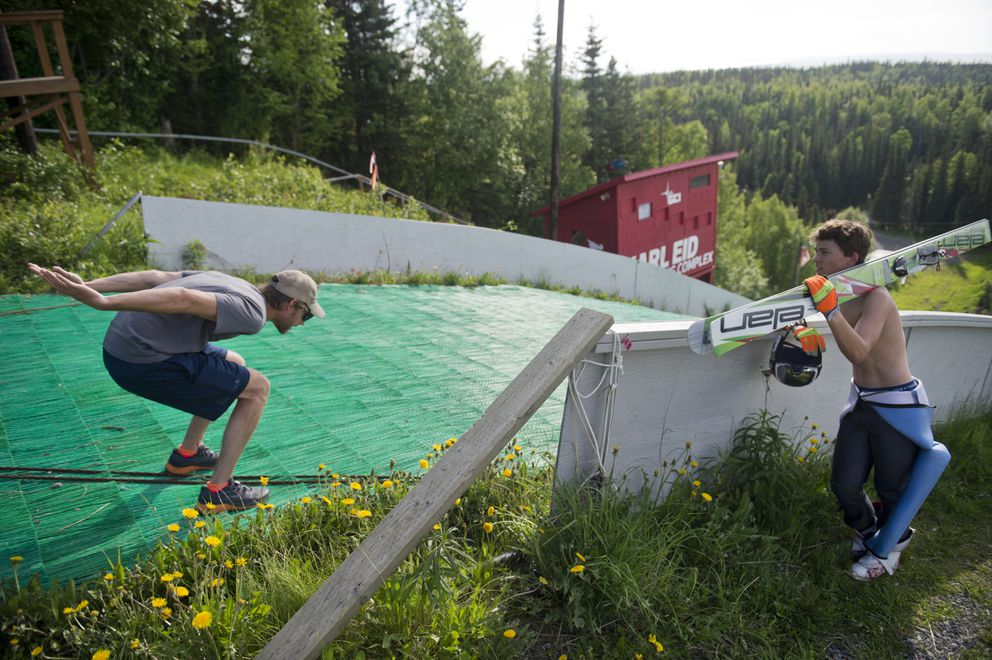Coach Chris Lamb, left, talks with Carter Brubaker between jumps at a training session Monday. (Marc Lester / ADN)