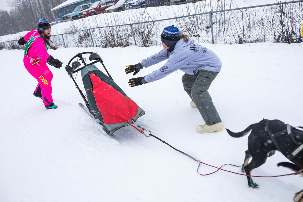 Shannon Wellmann, left, and Johanna Badalich catch a riderless sled in the 2-dog class race Saturday, Feb. 16, 2019 during the Junior World Championship Sled Dog Race at Tozier Track. Musher Hudson Wright was one of two mushers to lose their team during the 2-dog class race. (Loren Holmes / ADN)