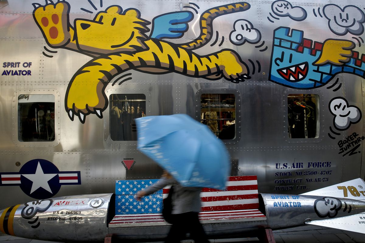 A woman walks by a bench painted with an American flag outside a fashion boutique selling U.S. brand clothing at the capital city's popular shopping mall in Beijing, Monday, May 13, 2019. Companies waited Monday to see how China decides to retaliate for President Donald Trump's latest tariff hike while forecasters warned their escalating fight over technology and trade might disrupt a Chinese economic recovery. (AP Photo/Andy Wong)