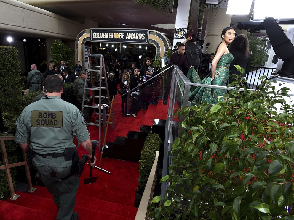 Law enforcement performs a security sweep of the red carpet as Jeannie Mai, right, prepares for the arrivals at the 76th annual Golden Globe Awards at the Beverly Hilton Hotel on Sunday, Jan. 6, 2019, in Beverly Hills, Calif. (Photo by Jordan Strauss/Invision/AP)