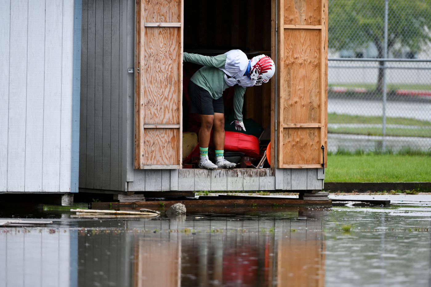 An East High player retrieves equipment from a shed during a rainy practice. (Marc Lester / ADN)