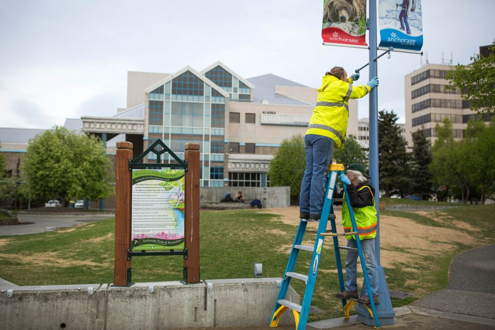 Municipal gardeners Tammy Calhoun, left, and Jackie Bennett prepare light poles for hanging flower baskets in Town Square Park on May 11, 2016. (Loren Holmes / Alaska Dispatch News)