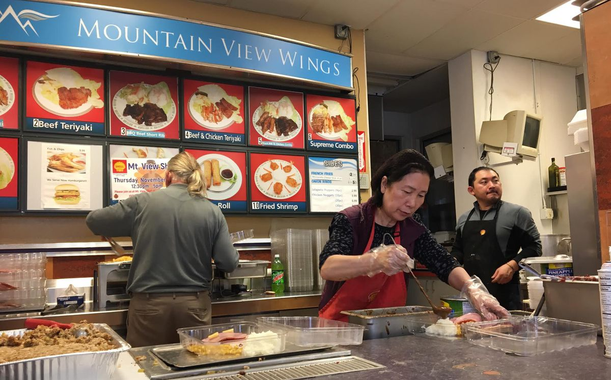 Insook Baik, the owner of the Shell gas station on Mountain View Drive, ladles gravy on mashed potatoes on Thanksgiving Day. She has served free meals at the gas station's convenient store for about eight years. (Tegan Hanlon/ADN)