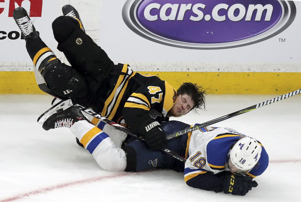 Boston Bruins' Torey Krug (47) and St. Louis Blues' Robert Thomas (18) crash to the ice during the third period in Game 1 of the NHL hockey Stanley Cup Final, Monday, May 27, 2019, in Boston. (AP Photo/Charles Krupa)