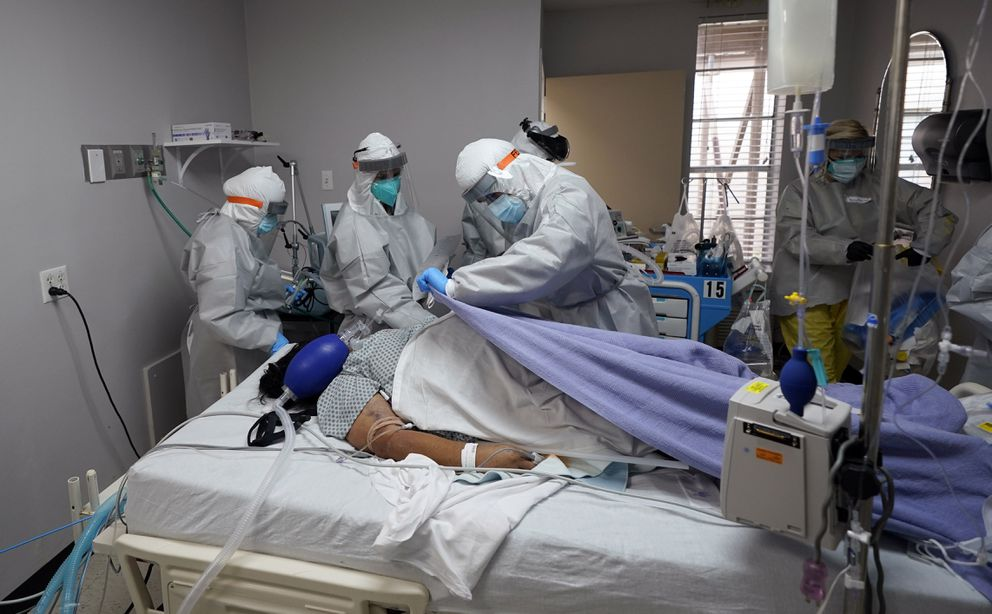 A blanket is pulled to cover the body of a patient after medical personnel were unable to to save her life inside the coronavirus unit at United Memorial Medical Center, Monday, July 6, 2020, in Houston. (AP Photo/David J. Phillip)
