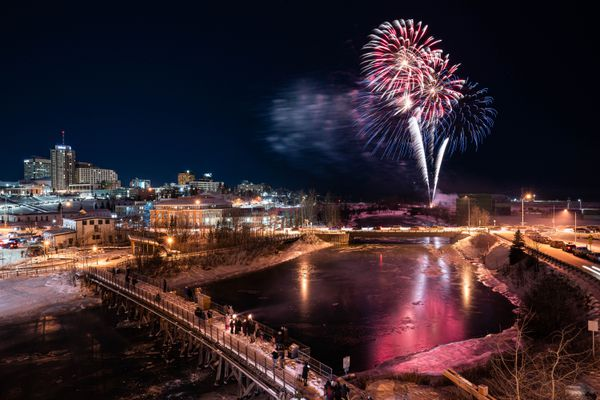 Fireworks are reflected in a frozen Ship Creek on New Year's Eve, Thursday, Dec. 31, 2020 in downtown Anchorage. (Loren Holmes / ADN)