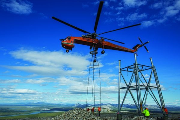 A crew with STG Inc. waits for a heavy-lift helicopter to deliver a section of tower as part of the $300 million-plus TERRA project that was completed last year by GCI to connect more than 80 rural communities with broadband internet. (Photo courtesy STG Inc.)