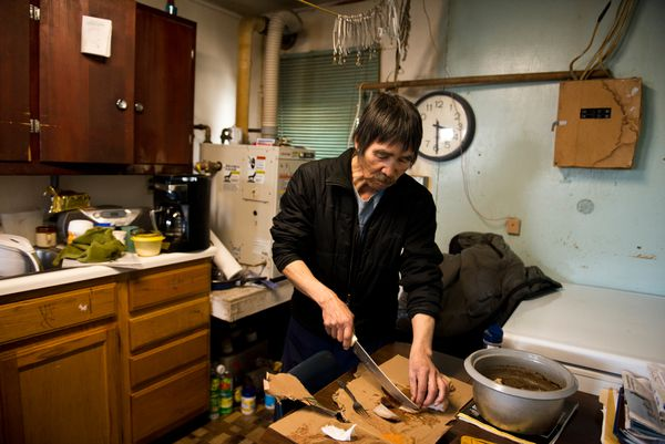 Roy Waghiyi slices walrus in his in Savoonga home. Waghiyi pairs a thin slice of meat with a thin slice of fat dabbed together in seasoned salt for each bite. (Marc Lester / Alaska Dispatch News)