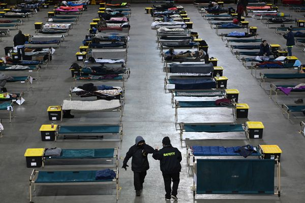 Two people elbow bump while walking through the socially distanced cots on the floor the Sullivan Arena where Bean's Cafe operates a Mass Emergency Shelter on Wednesday, Feb. 24, 2021. (Bill Roth / ADN)