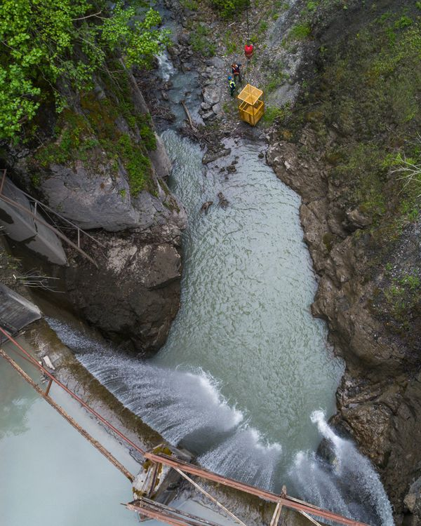 Workers, lowered by a crane, inspect a staging area downstream from the Eklutna dam on Wednesday. The concrete dam will be dismantled in pieces, and those will be crushed and tucked into corners of the canyon, as removing them by crane would be too expensive. (Loren Holmes / Alaska Dispatch News)
