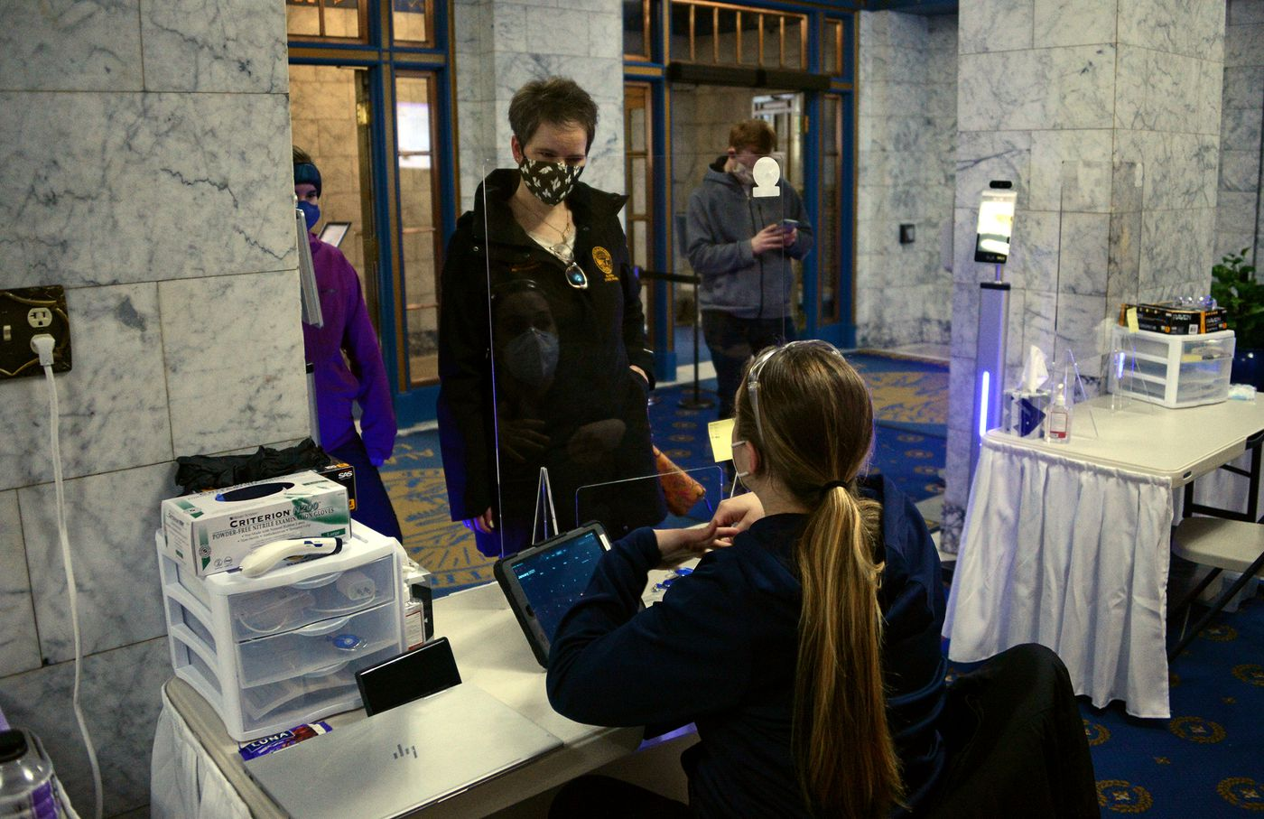 Rep. Sarah Vance, R-Homer, talks to a COVID-19 screener in the lobby of the Alaska State Capitol on Wednesday, Jan. 13, 2021. At background is Rep. David Eastman, R-Wasilla. (James Brooks / ADN)