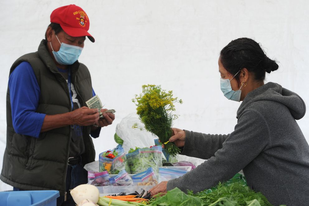 Peter Domingo purchased produce grown by Bhai Subba at the Grow North Farm along Mountain View Drive on Sunday. (Bill Roth / ADN)
